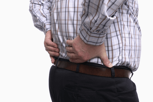 a man suffering from lower back pain and holding his lumbar area